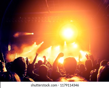 Concert lights over a crowd clapping