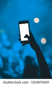 Concert poster.Popular music festival fan films popular singer on stage in nightclub.Silhouette of young person with smart phone filming famous dj party in the club.Empty white screen on mobile phone