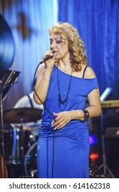 Concert in the restaurant. A middle-aged woman, of European appearance, sings into a microphone.