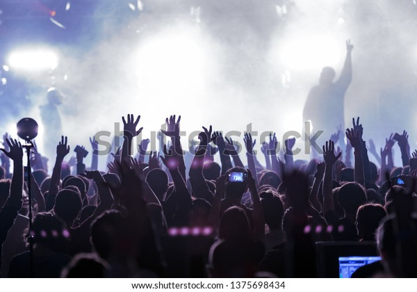 concert, silhouettes of happy people raising up hands, Music show. Bright scene lighting in club. Fans burn red flares at hip hop