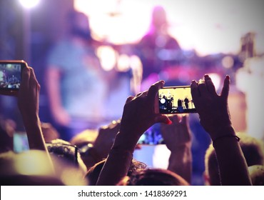 concert spectators photograph the singer who performs on stage with their mobile phone