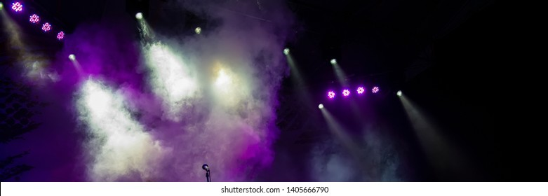 Concert stage lighting in the fog and microphone. Web banner.