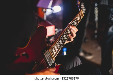 Concert view of an electric guitar player with vocalist and musical band in the background
