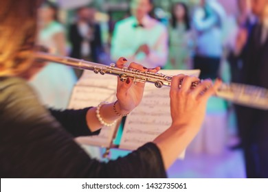 Concert view of a flutist flute player with  musical jazz band and audience in the background