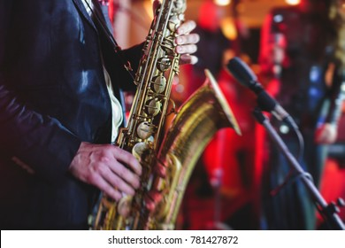 Concert view of a saxophone player with vocalist and musical jazz band in the background