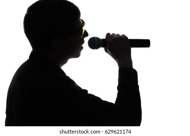 Concert of a young fashionable artist in colored glasses singing into the microphone on an isolated background in silhouette