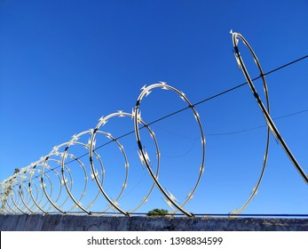 The concertina fence installed on a wall in a day with gorgeous blue sky and clouds