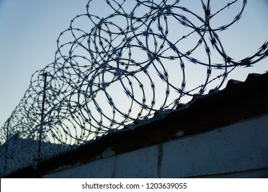 Concertina razor wire is pictured running the length of a wall.