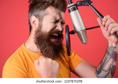 Concert&music concept. Bearded man singing with microphone. Brutal bearded guy singer with microphone on stage. Male lead vocalist singing in recording studio. Vocalist singing in condenser microphone