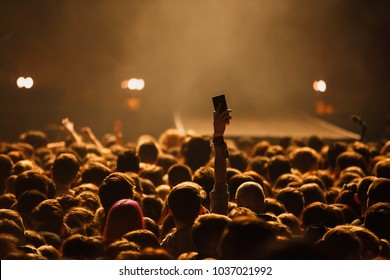 Concerts crowd in music hall.Fan puts hand up with smart phone.Music fans with mobile phones,photography on musical festival crowds.Young man takes picture with phone camera on rock concert.Gig poster