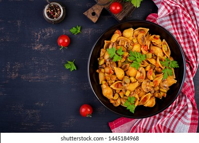 Conchiglie pasta. Italian pasta shells with mushrooms, zucchini and tomato sauce.  Top view