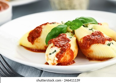 Conchigliei pasta stuffed with a ricotta cheese, mozzarella and basil leaves with extreme shallow depth of field.