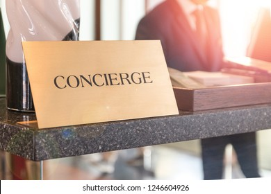 Concierge service desk counter with happy employee staff receptionist working in front of hotel with tourist guest business customer.