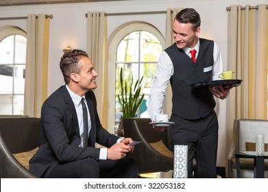 Concierge or waiter serving guest at hotel a cup of coffee