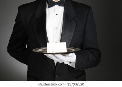 A concierge wearing a tuxedo holding a note card on a silver tray in front of his torso. Man is unrecognizable over a light to dark gray background.
