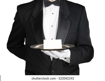 A concierge wearing a tuxedo holding a note card on a silver tray in front of his torso. Man is unrecognizable over white.