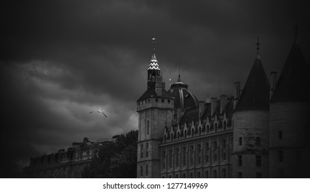 Conciergerie, former prison building. Paris, France. Gull flying in cloudy gloomy sky. Overcast. Black and white photo.