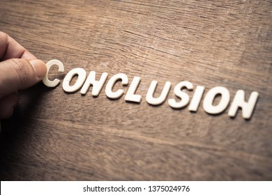 CONCLUSION, closeup hand place a wood letter into the word for review content concept