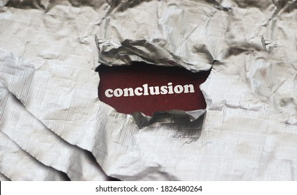 Conclusion word under silver foil torn paper. Education n business concept.