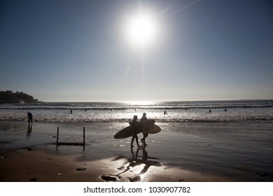CONCON, CHILE-JUNE 6, 2015: Surfer walks along the beach after a fun time in the water. Image is backlit and features the subject in silhouette in Concon, Chile on June 6, 2015