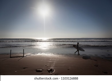 CONCON, CHILE-JUNE 6, 2015: Surfer walks along the beach after a fun time in the water. Image is backlit and features the subject in silhouette. in Concon on June 6, 2015