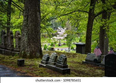 Concord, MA / USA - May 19 2018: Lothrop tombstone in Authors Ridge. USA flags and dogwood trees visible at the background.
