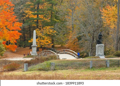 Concord, Massachusetts - October 24, 2020: The Minute Man statue and North Bridge  at Minute Man National Historic Park with fall foliage as background, Concord Massachusetts.