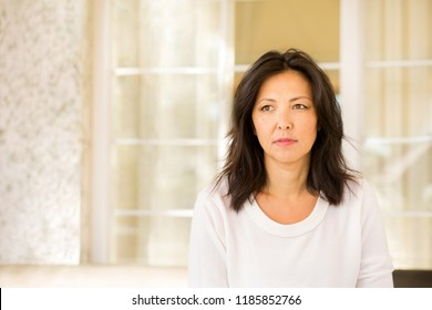 Concrened woman looking worried and praying on a sofa.