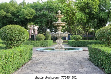 concrete architecture fountain in the garden with green tree and walkway