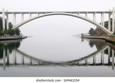 Concrete Arrabida bridge over Douro river with reflection in a foggy morning, Porto, Portugal