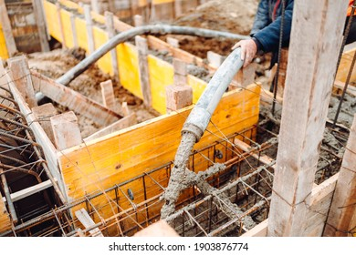 concrete automatic pump working and pouring cement into wooden frames at house construction