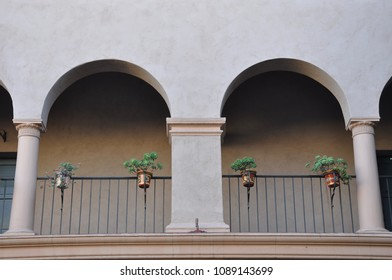 Concrete balcony with plants hanging on the railings