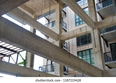 Concrete Beams Inside Building Construction and Hanging Lights Next to Residential Building