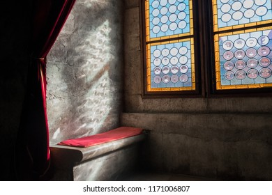A concrete bench with a red pillow on top of it next to colored window in a one of the biggest and prettiest medieval castles Corvin Castle in Hunedoara, Romania