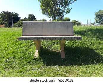 concrete bench in a square with a green lawn and a blue sky with a sunny day