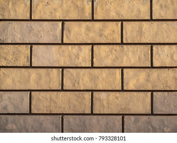 Concrete block wall texture in the yellow sunlight