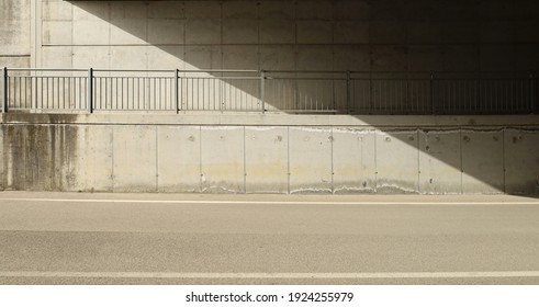 Concrete block wall of an underpass with a footpath and a railing in the middle. Side light and shadow. asphalt road in front. No people. Background for copy space.