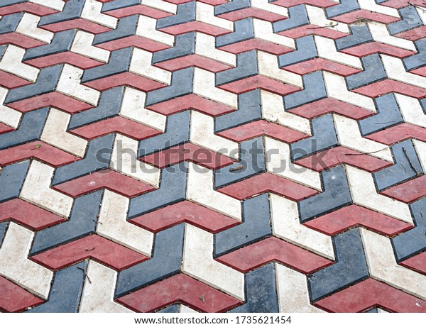 Concrete blocks for wall sidewalk or pavement different colors. Red, blue and white tiles creating geometric background. Cobblestones in a park and outdoors.