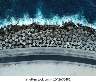 Concrete breakwaters. Seascape with concrete tetrapodes to protect coastal structures from destructive impact of storm sea waves. Tetra-pods, concrete blocks. Strengthening of concrete sea. Breakwater