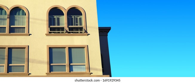 concrete building with ark windows yellow wall and blue sky
