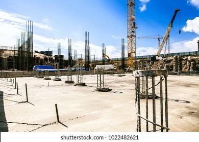 Concrete building construction site. Rebar for concrete pillars. Building site with cranes, steel rebar of concrete piles, foundation slab.