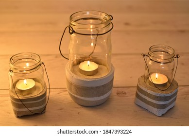 Concrete candle lanterns. Three concrete and glass candle light holders for indoor and outdoor decor. Concrete art concept. Ambient light. Selective focus.