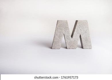 Concrete Capital Letter M isolated on white background. 3D object