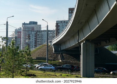 Concrete car overpass in the city center. Busy car traffic under the overpass. Concrete overpass with massive concrete supports.