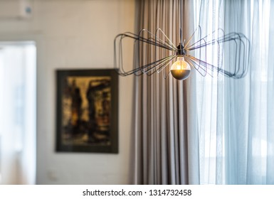 Concrete ceiling and stylish lamp. Interior of a modern apartment.