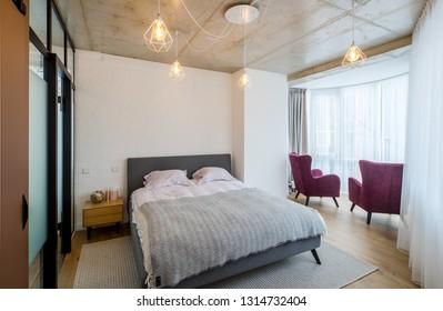 Concrete ceilings, wooden floor. Interior bedroom in the apartment.