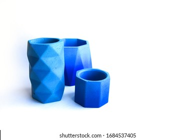Concrete cement blue pots. Hand made concrete planters for succulents and cacti. Empty cup isolated on white background. Polygonal geometric shape for home decor.