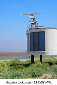 the concrete coastguard station in fleetwood with radar antennae with crass covered dunes leading to the beach on a summers day in bright sunlight with blue sky
