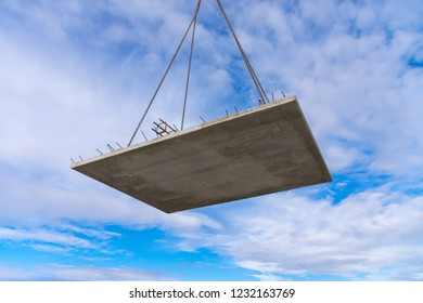 Concrete component hangs on the crane chain in front of blue sky