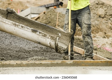 Concrete construction contractor installing a sidewalk, curb and storm drainage gutter on a new urban road street project